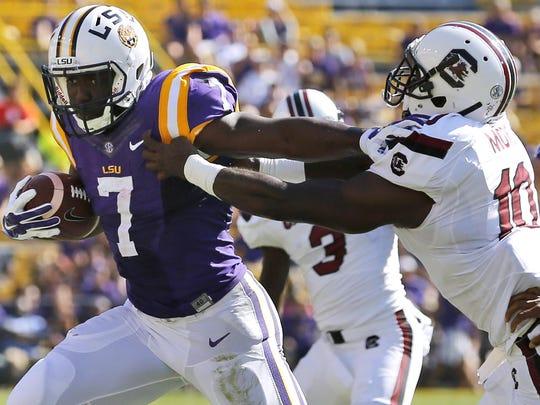 LSU running back Leonard Fournette (7) stiff arms South Carolina linebacker Skai Moore (10) during a 2015 game in Baton Rouge, Louisiana.