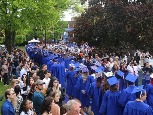 Hundreds of graduates walk through campus into the