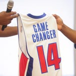 Former Detroit Piston Earl Curleton hands a jersey to Michigan Technical Academy third-grade teacher Andrew Knox at school in Detroit on Tuesday.