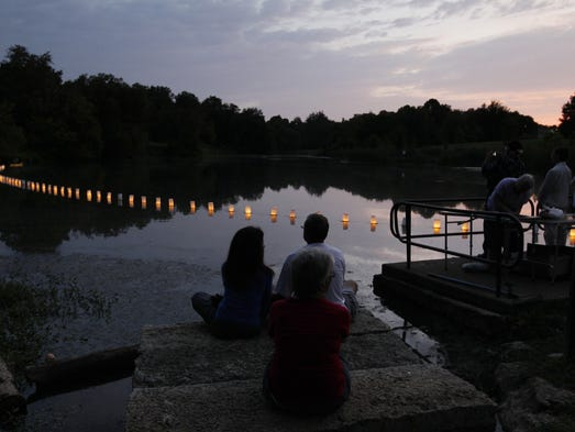 Members of the crowd sit along side the lake and watch the glow of the lanterns on the water during a lantern floating ceremony at Willow Lake in Cherokee Park in Louisville, Kentucky.  The ceremony marked the 67th anniversary of the atomic bombing of Hiroshima and Nagasaki.    August 4, 2012