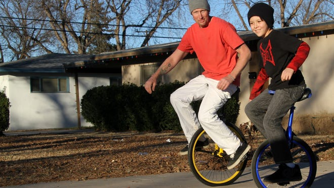 Robbie and Ocean Hutchins raced on their unicycles in their driveway.