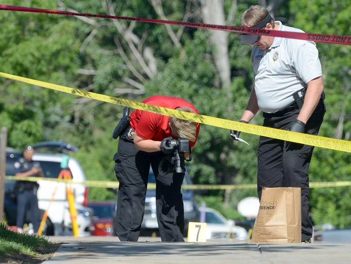 Fort Collins Police Department, forensic detectives, Tamara Tracy, left, and Neal Hisan, photograph a piece of evidence as police investigate an officer-involved shooting outside the emergency room at Poudre Valley Hospital Thursday June 5, 2014.