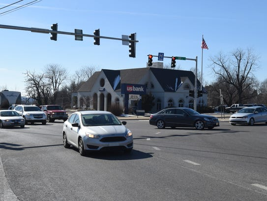Drivers ease their way through the intersection of