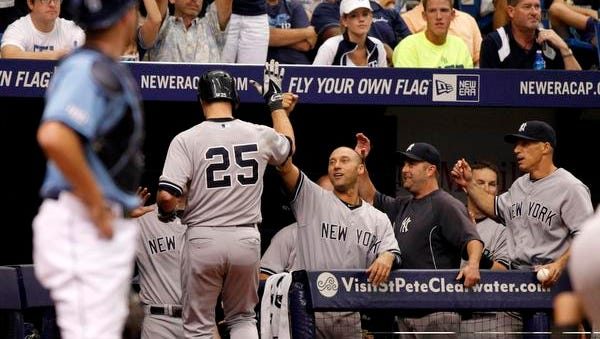 Yankees first baseman Mark Teixeira is greeted by, from left, Derek Jeter, hitting coach Kevin Long and manager Joe Girardi after hitting a solo home run during the eighth inning Sunday at Tropicana Field. The Yankees defeated the Tampa Bay Rays 4-2.