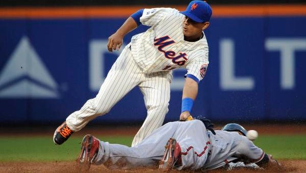 The Atlanta Braves' Emilio Bonifacio steals second base as Mets shortstop Ruben Tejada fails to field the throw at Citi Field on Thursday night.