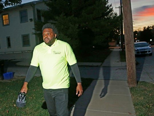 Security guard Joshua Holmes walks through the neighborhood