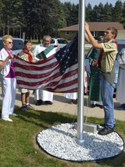 Pulaski High School sophomore Jacob LeMere, right, sets the American flag on a new flagpole outside St. Joseph Church in Oneida during a post-Mass dedication Sept. 6. Longtime church member Lorraine Pasowicz, who donated the new flagpole to the church in memory of her husband Edmund, holds the flag.
