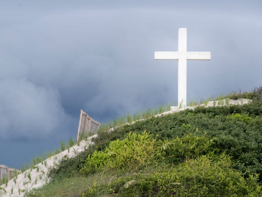 Storm clouds gather in the sky above the Island Cross on Fort Pickens Road on Pensacola Beach on Tuesday, July 18, 2017.