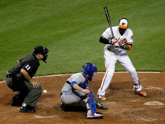 A pitch slips past Toronto Blue Jays catcher Josh Thole, center, as home plate umpire Tony Randazzo, left, and Baltimore Orioles' Adam Jones, right, watch in the 10th inning of a baseball game in Baltimore, Wednesday, April 20, 2016. Caleb Joseph scored on the play, and Baltimore won 4-3. (AP Photo/Patrick Semansky)