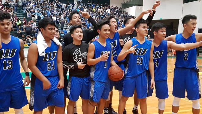 Members of the St. Paul Warriors celebrate after their 63-56 win over the Father Duenas Friars to win the IIAAG Boys Basketball championship March 10 at a packed University of Guam Calvo Field House.