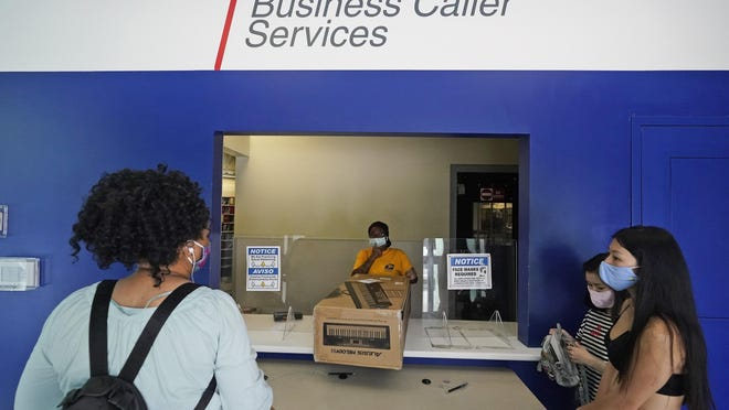 A postal worker, center, attends to customers at the Flagler Station post office, Tuesday, Aug. 25, 2020, in Miami. The pandemic has pushed the Postal Service into a central role in the 2020 elections, with tens of millions of people expected to vote by mail rather than in-person. At the same time, Trump has acknowledged he is withholding emergency aid from the service to make it harder to process mail-in ballots, as his election campaign legally challenges mail voting procedures in key states.