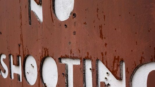 A 'no shooting' sign in the Pike National Forest near Sedalia, Colo., is peppered with bullet holes.