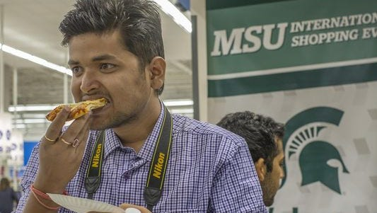 MSU freshman Mayank Tiwari from India, tries a piece of pizza provided by the Okemos Meijer as part of an annual welcoming for international students Sunday.