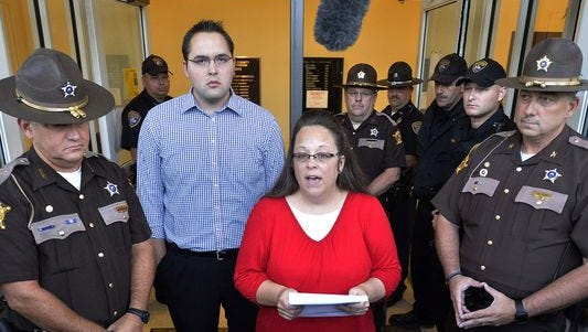 Surrounded by Rowan County (Ky.) Sheriff's deputies, Rowan County Clerk Kim Davis, center, with her son Nathan Davis standing by her side, makes a statement at the front door of the Rowan County Judicial Center in Morehead, Ky., on Monday, Sept. 14, 2015. Davis announced that her office will issue marriage licenses under order of a federal judge, but will not have her name or office listed.