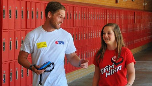 Zane Schultz, 26, the co-founder and heart screening manager of Who We Play For, walks at Cocoa Beach Jr. / Sr. High with Cristina Cinca.