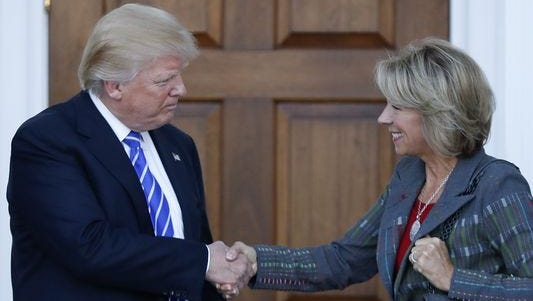 President-Elect Donald Trump, left, shakes hands with Michigan philanthropist and school choice advocate Betsy DeVos. DeVos is Trump's nominee for education secretary.