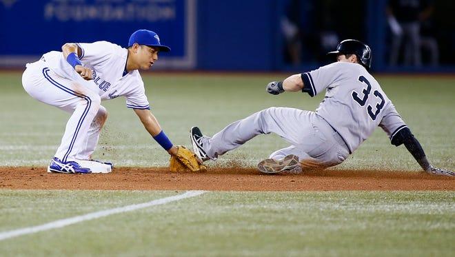 Toronto Blue Jays second baseman Munenori Kawasaki (66) catches New York Yankees third baseman Kelly Johnson (33) stealing in the eighth inning at Rogers Centre.