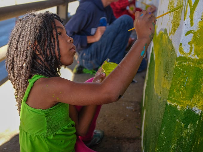 Mary Wilson, 6, does her part on the paint-by-number