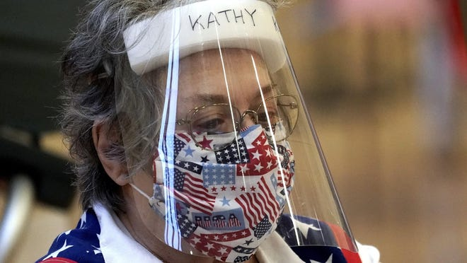 Harris County election clerk Kathy Kellen wears a mask and face shield while working at a polling site, Monday in Houston.