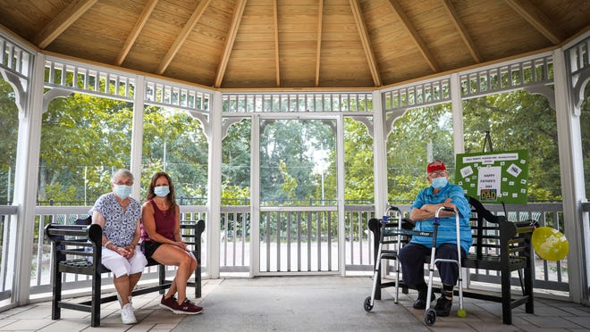 Raymond Fluet, right, celebrates Father's Day with his wife, Doris Fluet, left, and their daughter, Mary Peters, center, as they sit inside a screened gazebo at Holy Trinity Nursing and Rehabilitation Center in Worcester on Sunday.