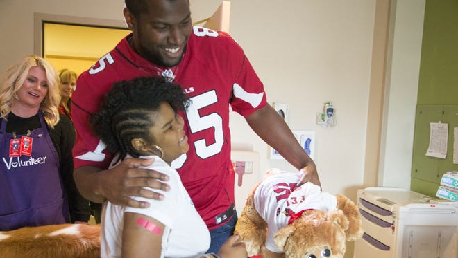 """Tight end Darren Fells of the Arizona Cardinals football club hugs patient Aaliyah Murphy, 13 during the annual """"Teddy Bear Express"""" visit at Phoenix Children's Hospital on Dec. 22, 2015."""