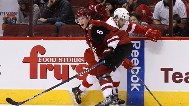 Connor Murphy (5) of the Coyotes tries to check Darren Helm of the Red Wings into the boards during the first period of an NHL game at Gila River Arena in Glendale, Az., on Thursday, January 14, 2016.