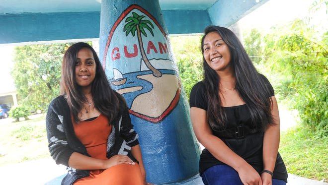 Former AmeriCorps members Erusa Perkin, 23, left, and Grace Billimon, 23, pose for a photo at a bus stop in Chalan Pago on April 2. The structure is one that they helped to paint as a community project while serving with Sanctuary Inc.'s AmeriCorps program. Del. Madeleine Bordallo has introduced Congressional legislation to allow nonimmigrants to participate in national service programs.