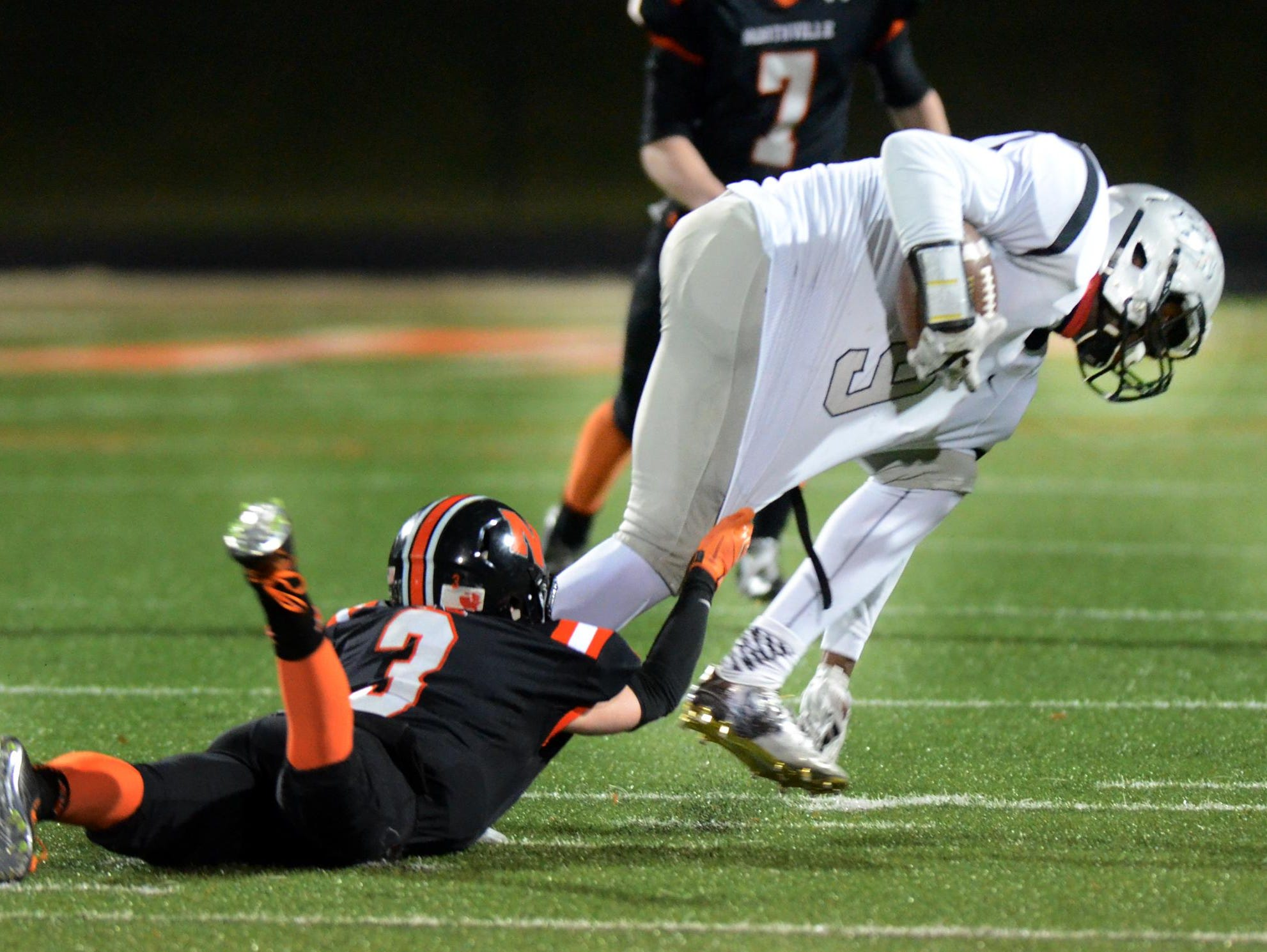 Northville's Zachary Prystash (left) tries to trip up Plymouth senior wide receiver Victor Abraham.
