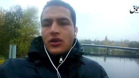 """This image made from video released by Amaq News Agency of the Islamic State group on Friday, Dec. 23, 2016 shows Anis Amri, a Tunisian suspect in the Berlin truck attack pledging allegiance to its leader Abu Bakr al-Baghdadi and vowing to fight against what he calls """"the Crusader pigs."""" The video, which appeared to have been taken by Anis Amri himself, shows him standing on a footbridge in the north of Berlin, not far from where he allegedly hijacked the truck used in the attack that killed 12 people and injured dozens more at a Christmas market on Monday."""
