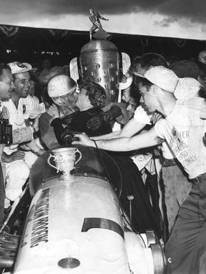 Johnnie Parsons didn't let the rain bother him as he indulged in an extended congratulatory kiss from actress Barbara Stanywck after winning the 1950 Indianapolis 500.