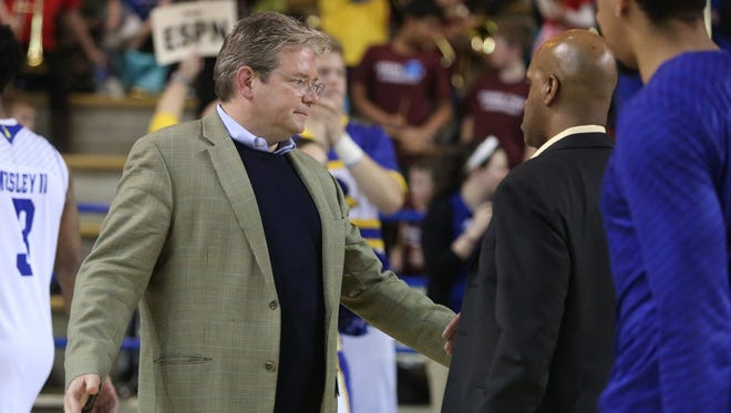 Interim Delaware athletic director Matt Robinson (left) greets men's basketball players and coaches, including deposed Monte Ross, after Delaware's 94-79 loss to William and Mary at the Carpenter Center this season.
