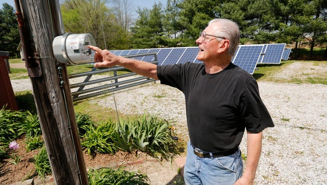"Jim Couk checks the net meter connected to his solar panels Wednesday, April 26, 2017, at his farm near Pyrmont. By checking the net meter, Couk can see if energy is going to the power grid, or if he is buying energy. Couk began installing solar panels at his farm in 2013. ""You have to think beyond yourself and think about what you are doing for the environment,"" he said."