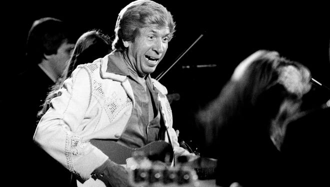 Buck Owens, center, performs at the International Fan Club organization banquet and show during Fan Fair at Municipal Auditorium on June 8, 1977.