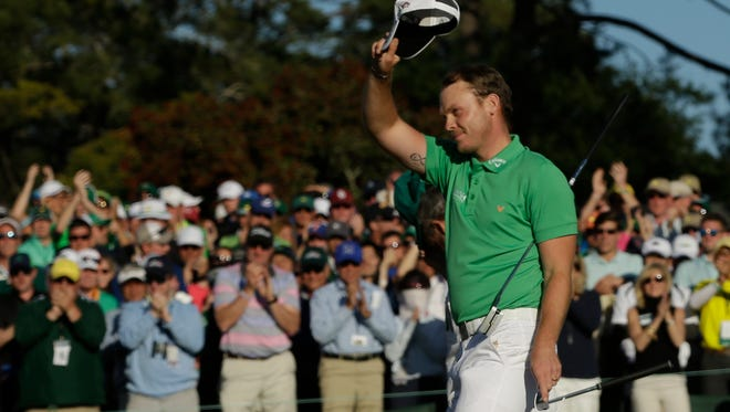 Danny Willett waves to the crowd after completing the 18th hole during the final round of the 2016 The Masters golf tournament at Augusta National Golf Club.