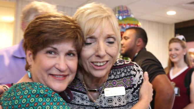 Pam Lavender hugs Janie Russ at a new hotel opening in Monroe.