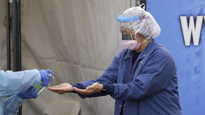 In this March 17, 2020, photo, Theresa Malijan, a registered nurse, has hand sanitizer applied on her hands after removing her gloves after she took a nasopharyngeal swab from a patient at a drive-thru COVID-19 testing station for University of Washington Medicine patients in Seattle. The Associated Press has found that the critical shortage of testing swabs, protective masks, surgical gowns and hand sanitizer can be tied to a sudden drop in imports of medical supplies.