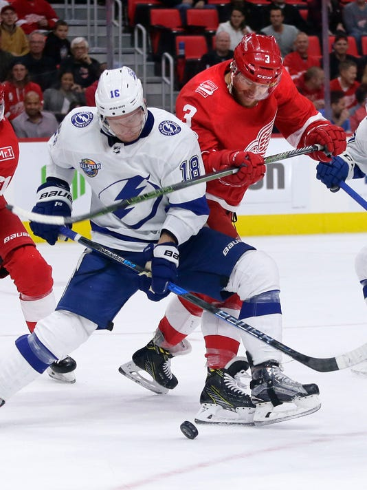 Detroit Red Wings defenseman Nick Jensen (3) battles for the control of the puck with Tampa Bay Lightning left wing Ondrej Palat (18), of the Czech Republic, during the first period of an NHL hockey game Monday, Oct. 16, 2017, in Detroit. (AP Photo/Duane Burleson)