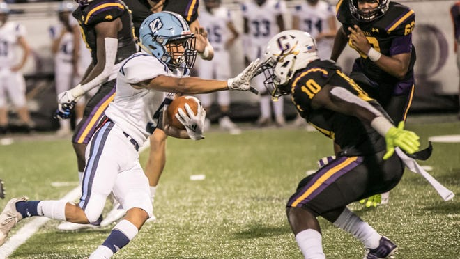 Calvary Day's Juwan Johnson (10) is stiff-armed by North Cobb Christian's Briyar Powers (5) but still makes the tackle during first-half action Friday at Calvary. North Cobb Christian won 34-0.