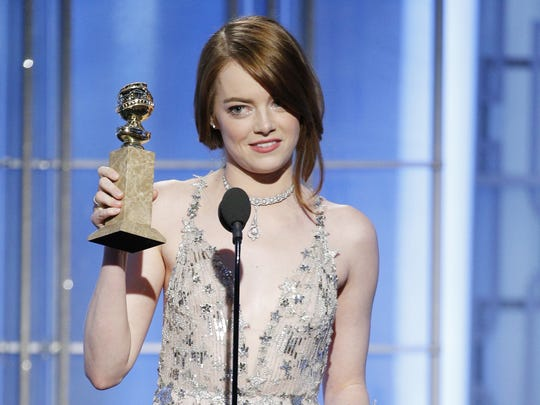 Emma Stone takes her trophy for best actress in a musical or comedy for 'La La Land.'
