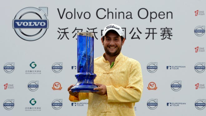 Alexander Levy of France poses with his winning trophy after the final round of the Volvo China Open at Genzon Golf Club in Shenzhen, southern China.