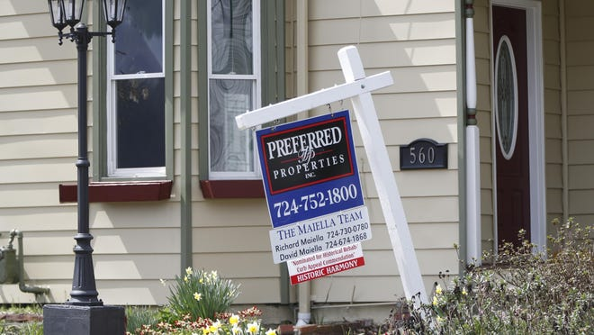 This April photo shows a real estate company sign that marks a home for sale in Harmony, Pa. Existing home sales in the U.S. plunged 9.7% in May for the third straight monthly decline.