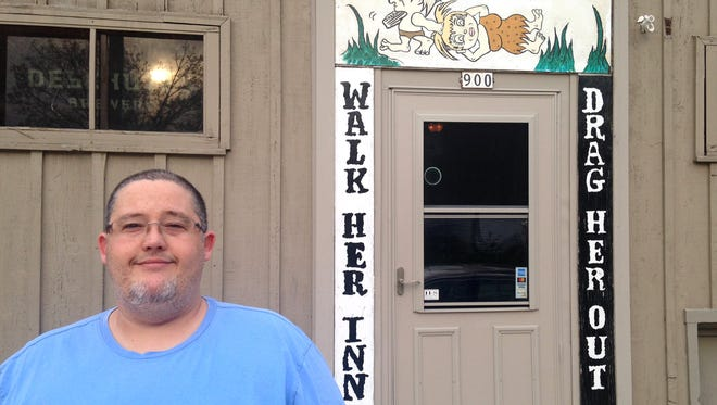 Kristian Plumeri, who owns the bar with his wife, Diane, stands in front of the signs at the entrance. A woman complained that the signs and wording promote violence and a negative image of women. Her social media concerns went viral.