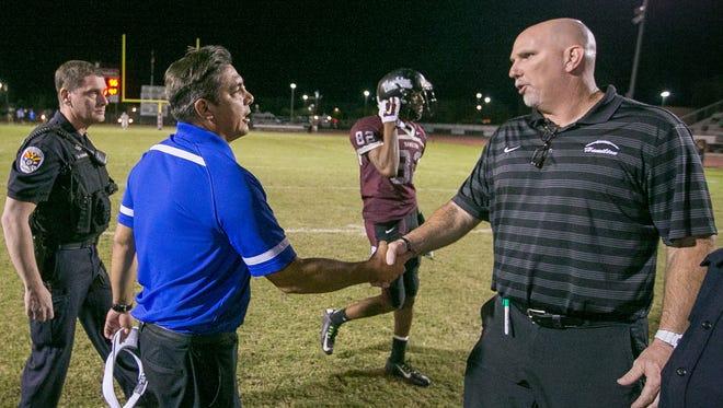 Chandler High head coach Shaun Aguano shakes hands with Chandler Hamilton head coach Steve Belles after Chandler won their high school football game on Thursday, October 2, 2014.