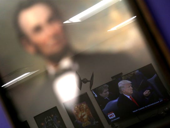 A TV image of Donald Trump is reflected in a portrait