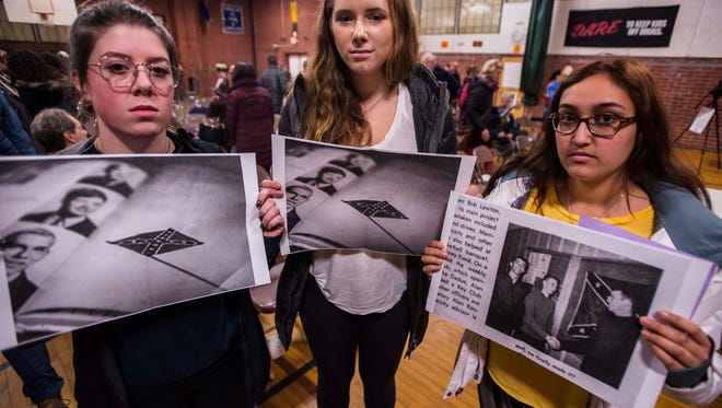 """From left, South Burlington High School Student Diversity Union members Lauren Wickens, Sadie Jones and Sabrina Choudhary hold copies of year book pages from the 1960s showing the Confederate flag being flown at the school and displayed in hallways and the gymnasium. The year books, uncovered in a Burlington Free Press investigation, countered claims that the """"Rebel"""" name was not tied to the Confederate south."""