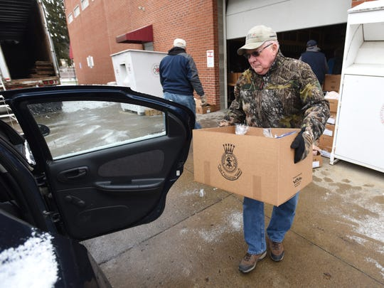 Galen Thompson carries a box of food to a waiting car on Thursday, during the first of two Salvation Army disburtion days this month.