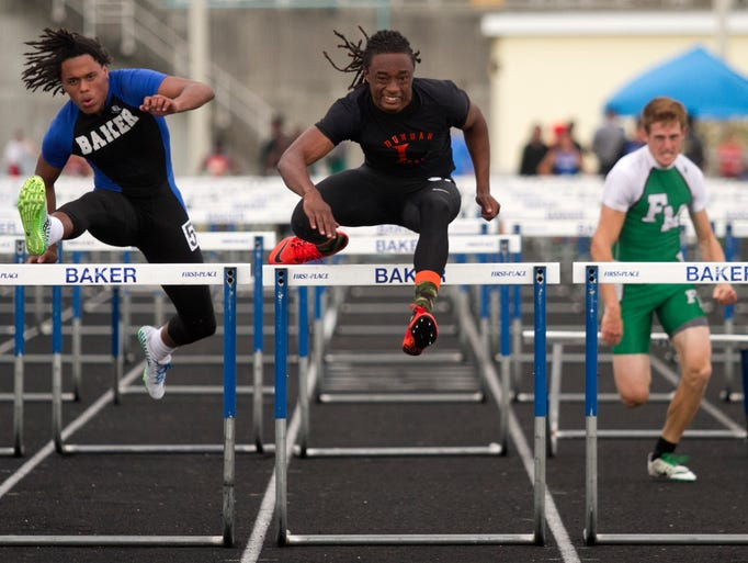 Mike Shields, left, of Ida Baker, Terrance Adams of Dunbar and Ben Atkinson of Fort Myers compete in the 110 hurdles in the LCAC track meet on Thursday at Ida Baker High School.