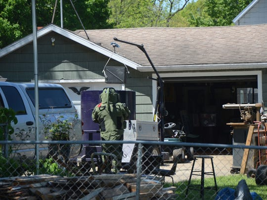 Detective Scott Silverman of the Battle Creek Police Department Bomb Unit places the grenade in a container.