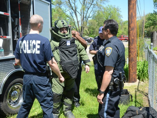 Detective Scott Silverman puts on a safety suit before going into a building to retrieve an unexploded grenade.