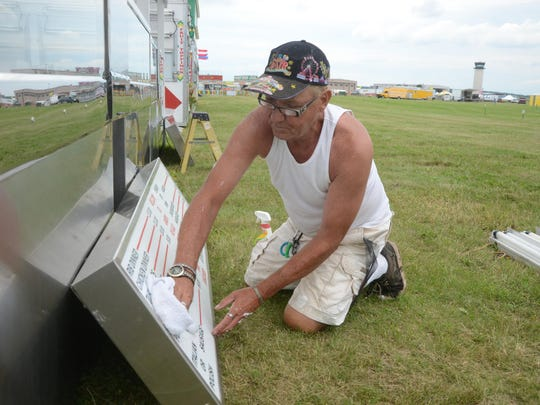 Jimmy Hockman of Tampa, Fla., cleans a menu sign outside a food truck Monday at the Field of Flight grounds.